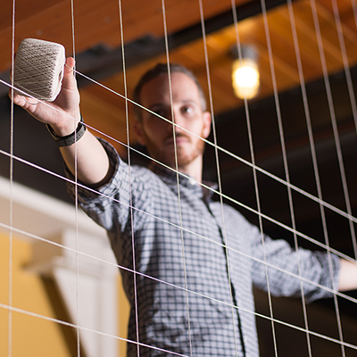 man behind grid of string with spool of string