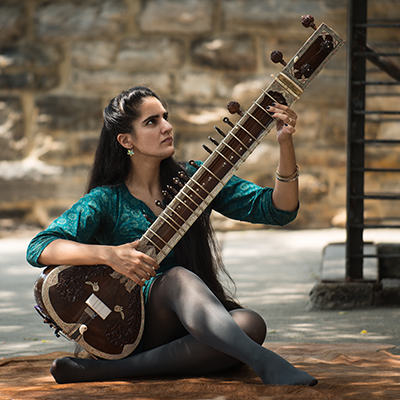 woman playing sitar outside