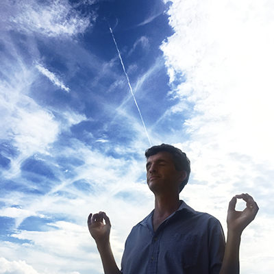 man meditating with sky background