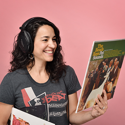 woman wears headphones and holds vinyl records