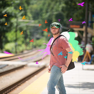 mean with headphones waits at train tracks