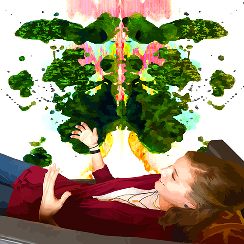 woman laying down in therapy with Rorschach painting as the background
